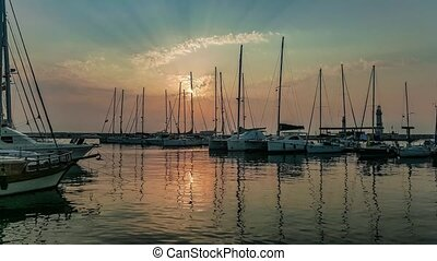Yachts moored at marina in a row under the sunrise. - Yachts...