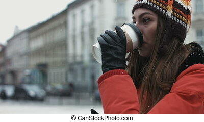 Stand-up of an attractive woman drinking coffee ourdoors and...
