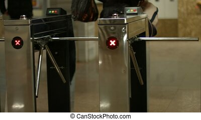 People pass through the turnstiles Check point Turnstiles in...