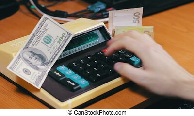 Counting Money On a Retro Calculator - Businessman counts...