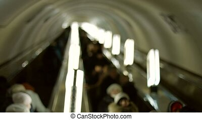 People go on the escalator Passengers descend into the...