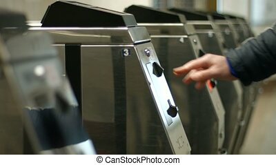 Passengers pass through the turnstile. People pay the fare....