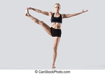 Extended Hand to Big Toe pose - Sporty beautiful young woman...