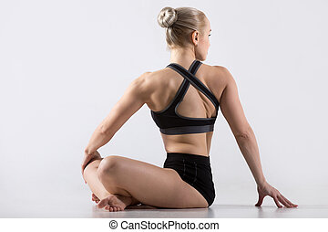 Parivrtta Sukhasana pose - Sporty beautiful young woman...