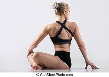 Parivrtta Sukhasana pose - Sporty beautiful young woman...