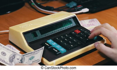 Counting Money On a Old Calculator - Businessman counts the...