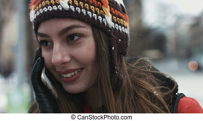 Close-up portrait of a young female sweet talking on telephone outdoors. Girl smiling while have a conversation on cellphone.