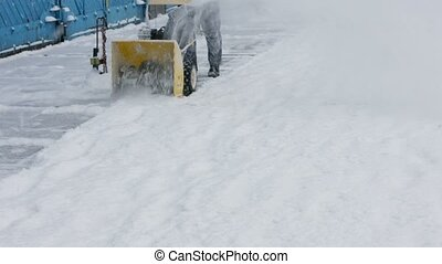 Janitor cleans snow tractor.