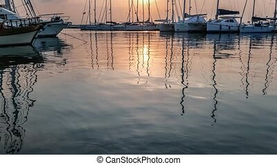 Yachts masts reflection in the sea water under the twilight.