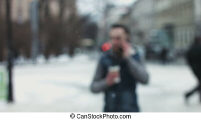 Young man moving towards camera with a takeaway coffee...