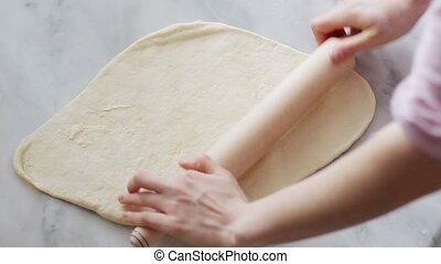 Woman rolling dough Chef rolling pastry sheets on table...
