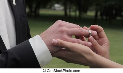 Bride putting wedding ring on groom's finger. Young couple...