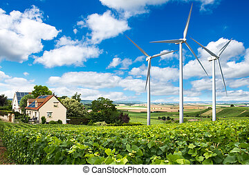 Houses with solar panels on roof and wind turbines nearby....