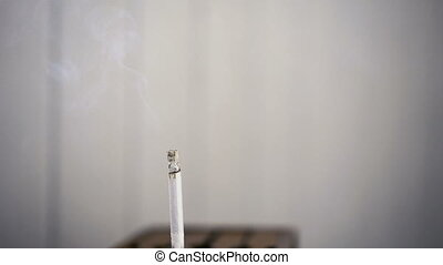 Cigarette burning and smoking time lapse, isolated on white...