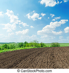 black agriculture field and white clouds in blue sky on...