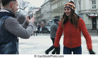 Guy taking photos of a beautiful girl outdoors by using his mobile device. Attractive woman making impressions on camera.