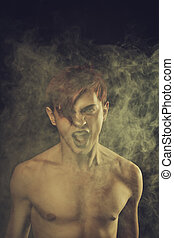 Sound of misery - Redhead young man screaming over dark...