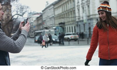 Young man taking pictures of his girlfriend whirling on...