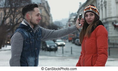 Handsome guy tries to take a picture of his girlfriend and scares her. Sweet couple having fun outdoors on the street while its snowing.