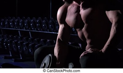 Torso of handsome athletic man in gym sitting and using dumbbell
