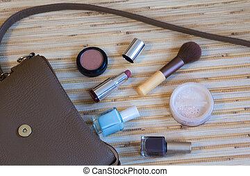 Open leather bag with women cosmetics (lip gloss, mascara,...