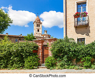 Green bushes and parish church in Italy. - Brick fence...