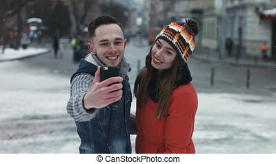 Young attractive couple making faces on camera. Man and woman taking photographs by using smartphone. Boy and girl make selfie outdoors in the middle of the european old town while its snowing.