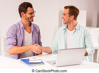 Attractive businessmen co-working - Two young attractive...
