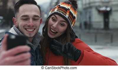Close-up portrait of a sweet couple showing tongues on camera; boy and girl embrace and make selfies by using mobile device.
