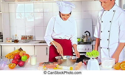 Mature chef man in hat teaches by woman dough. - Mature chef...
