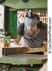 Craftsman with safety mask visor handles band saw in...