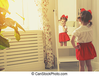 little girl child fashionista looking in the mirror at home...