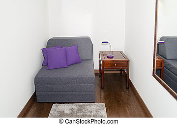 Comfy Gray Armchair with Purple Pillow near a Small Table