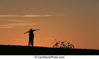 Silhouette of  Beautiful Couple With Tandem Bicycles. Man  Holds Her In His Arms And Dances Aganst The Sunset. Summer Nature Background with Beautiful Clouds in the Sky Close Up.