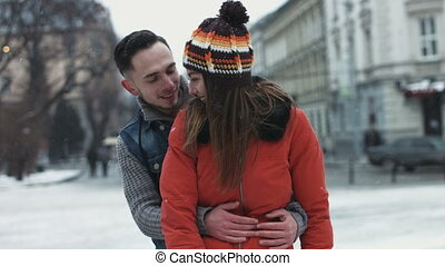 Young male trying to embrace his girlfriend outdoors. Happy sweet couple flirting with each other.