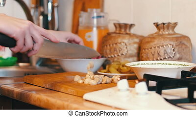 Woman Slices Mushrooms in the Kitchen - Woman cook in the...