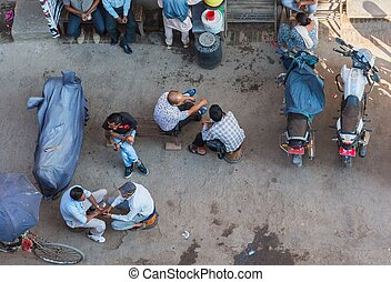Bird eye view of a busy street. People sitting and talking...