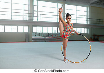 girl doing exercise with hoop, looking at camera - Little...