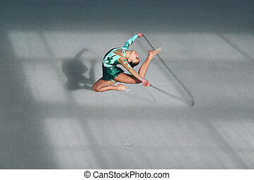 Beautiful gymnast in green suit jumping rope - Beautiful...