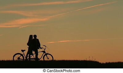 Romantic Couple with Tandem Bicycles Kissing Against Sunset....
