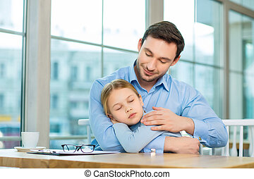 Handsome man holding his sleeping daughter