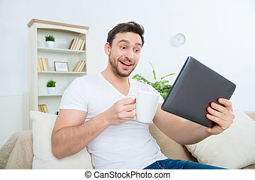 Young surprised man with cup and tablet - Look of surprise...