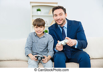 Handsome father enjoys playing video games with adorable son...