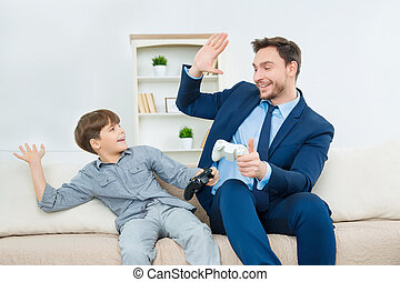 Handsome dad enjoying time with cute son - High five for...