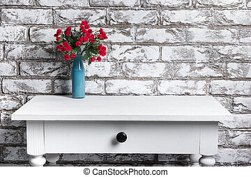 Red flowers in vase on the table on black and white brick...