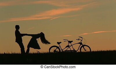 Romantic Couple with Tandem Bicycles Softly Holding Hands...