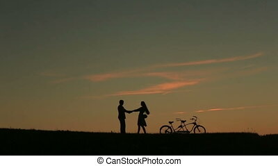 Romantic Couple with Tandem Bicycle Softly Kissing While...