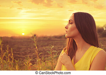 Beautiful woman profile portrait against sunset autumn field.