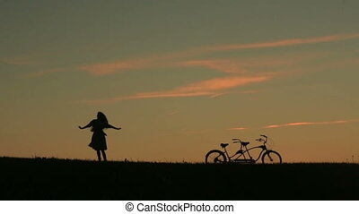 Silhouette of Romantic Girl With Tandem Bicycle Gracefully Dancing  Against Sunset. Summer Nature Background with Beautiful Clouds in the Sky Close Up