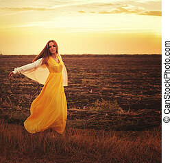 Fashion woman dressed in long yellow dress and white jersey...
